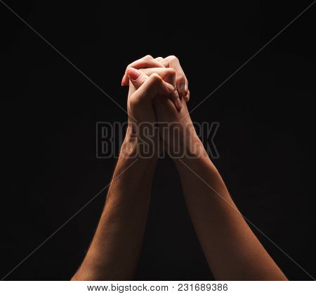 Male And Female Hands Clasped Together For Union Or Pray. Gestures On Isolated Black Studio Backgrou