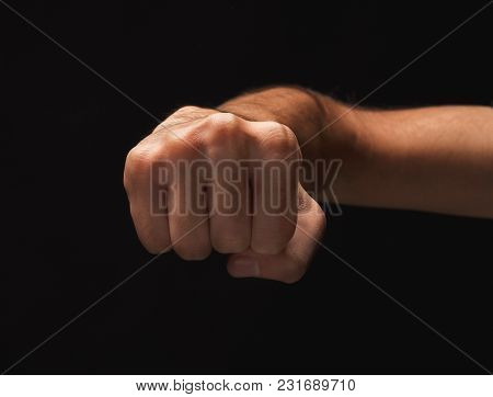 Male Hand Clenched Fist On Black Isolated Background, Low Key, Cutout. Strenght And Agression Concep