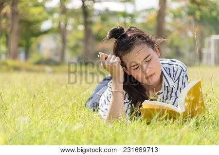 Beautiful Asian Women-student Reading Book On Grass, Against Background Of Summer Green Park.