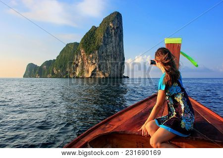 Young Woman Sitting In The Front Of A Longtail Boat Going To Phi Phi Leh Island, Krabi Province, Tha