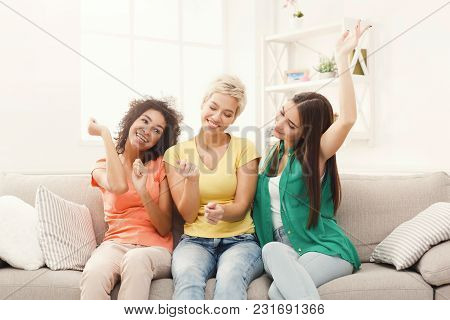 Happy Female Friends In Colourful Clothes Having Fun At Home. Three Young Women Laughing And Dancing