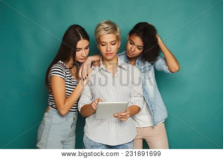 Three Female Friends Using Digital Tablet. Smiling Women Browsing Portable Computer At Blue Studio B