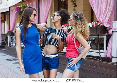 Three Happy Female Multiethnic Friends. Girls In Colourful Clothes Posing Against Cafe, Having Fun A