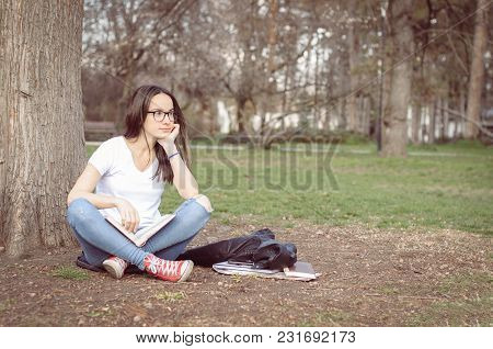 Beautiful Young School Or College Girl With Long Hair And Glasses Sitting On The Ground In The Park