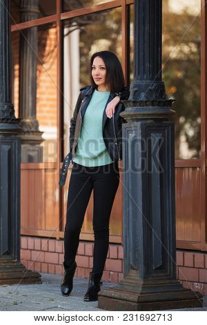 Young fashion woman walking in city street Stylish female model in black leather jacket outdoor