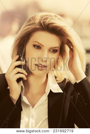 Young fashion business woman calling on cell phone in city street Stylish female model wearing black blazer and white shirt