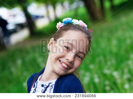 Cute Happy Girl Outdoors Enjoying Nature. Beautiful Teenage Girl With Long Hair Smiling At Sunny Day
