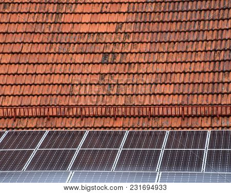 Old And Dirty Roof Of A House With New Solar Cells