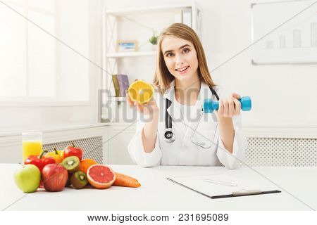 Young Dietitian With Orange And Dumbbell At Clinic. Smiling Woman Nutritionist Holding Fruit And Spo