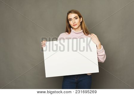 Young Woman With Blank White Paper. Attractive Smiling Girl Holding Advertising Sheet, Copy Space
