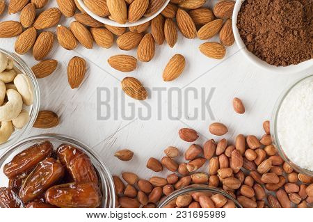 Culinary Background With Nuts, Dates, Coconut Flakes And Cocoa Powder On White Wooden Table.