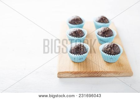 Homemade Healthy Gluten-free No Bake Brownie Energy Bites On Cutting Board On The White Table.