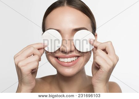 High Quality. Portrait Of Cheerful Young Woman Is Holding White Cotton Pads With Smile While Coverin