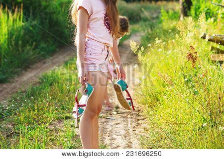 Beautiful Teen Girl Is Walking Barefoot At Sand Road On Warm Summer Day. Cute Teen Girl Feeling Very