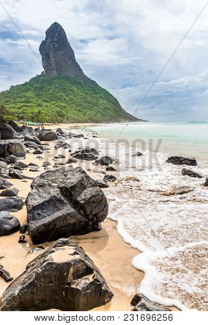 Fernando De Noronha, Brazil. Beach Of Conceicao. Conceiçao With Rocks In The Foreground.