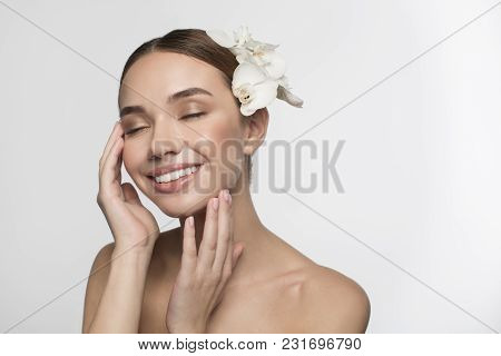 Perfect Skincare. Delighted Attractive Naked Girl With Flower In Hair Is Feeling Pleasure While Touc