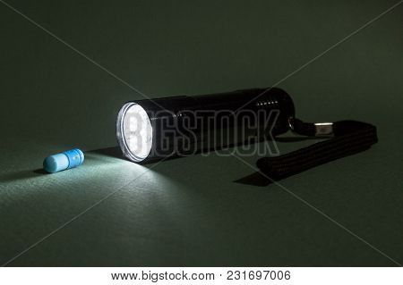 Concept Of Illicit Drug Trafficking And Quality Control. The Beam Of The Flashlight Illuminates The