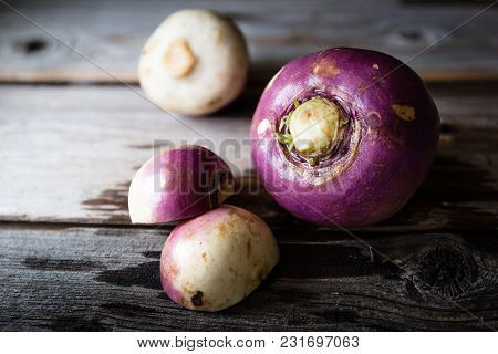 Horizontal  Close Up Image Of Three Raw Wet Rutabaga Lying On A Rustic Wood Background With Copy Spa