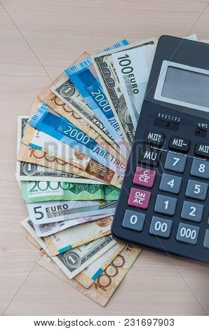 Different Banknotes Of Different Denominations Are Stacked In A Fan And A Calculator On The Table Ve