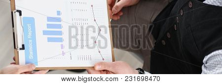 Male Hands Hold Clipboard Pad With Financial Statistics At Office Workspace Closeup. White Collar Ch