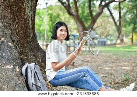 Education Concepts. Asian Women Reading Books In The Park. Beautiful Women Are Relaxing In The Park.