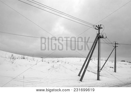 Supports And Wires Of The Electric Transmission Line On Snow-capped Hills Along The Road In The Clou
