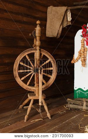 Old Wooden Spinning Yarn Wheel In Traditional Ukrainian Interior. Russian Folk Art.