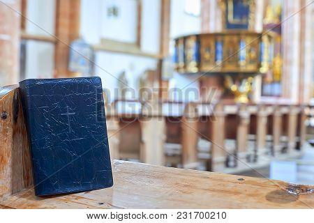 Black Holy Bible On Bench Inside Church