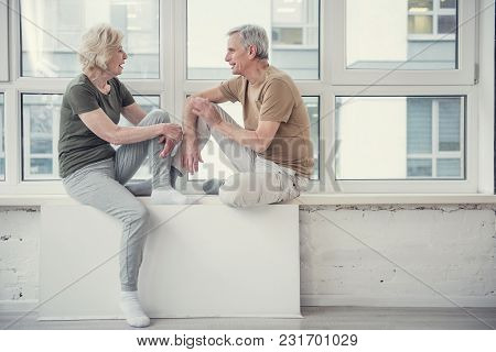 Side View Profile Of Two Joyful Pensioners Sitting On Windowsill And Talking. Copy Space In Right Si