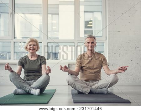 Portrait Of Cheery Aging Lady And Man Sitting On Carpets In Lotus Position And Smiling