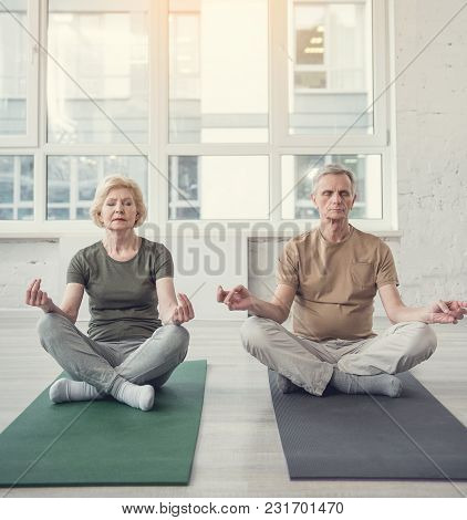 Portrait Of Peaceful Old Man And Woman Sitting In Lotus Position On Carpets With Eyes Closed