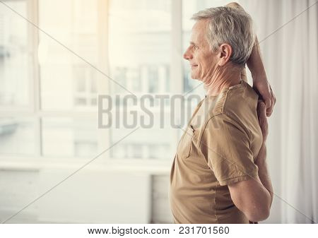 Side View Profile Of Cheerful Mature Man With Hands Hooked Behind His Back. Copy Space In Left Side
