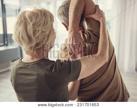 Oldish Man Standing With Hands Hooked Behind His Back. Mature Lady Assisting Him