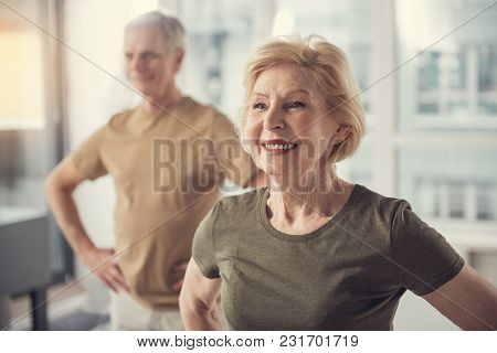 Portrait Of Content Good Looking Old Lady In Studio. Aging Male On Background