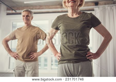 Happy Female And Male Standing With Their Hands On Hips. Focus On Woman