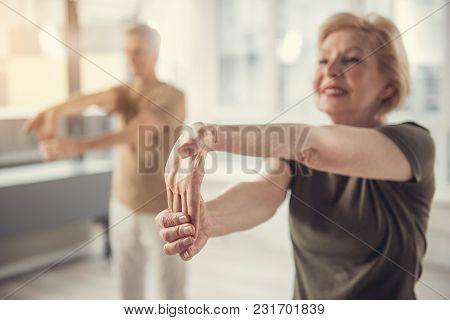 Joyful Aging Woman Standing And Stretching Her Hand. Old Male In Same Posture Standing On Background