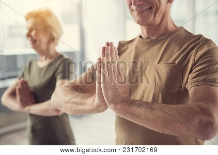 Elderly Group Practicing Yoga Asana. Focus On Pleased Aging Male Standing With Hands Clasped Togethe