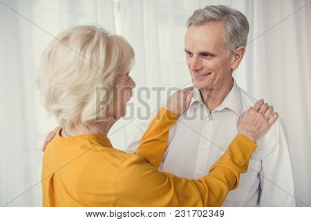 Caring Female Pensioner Looking At Her Smiling Elderly Husband, Her Hands Lying On His Shoulders. Wh