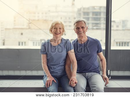 Portrait Of Elderly Wife And Husband Resting Near Window And Holding Hands Together. They Are Starin