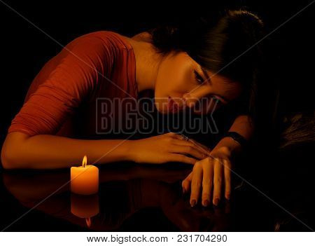 Low Key Portrait Of Young Pretty Woman With Candle And Reflection On Table