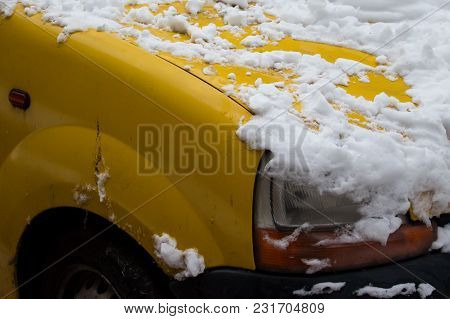 A Fragment Of A Bright Yellow Car Covered With White Snow