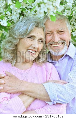 Happy Elder Couple Hugging On  Flowers Background