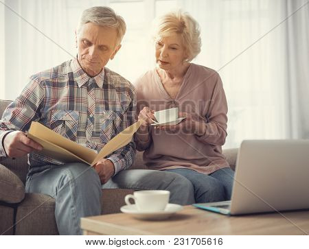 Calm Mature Man And Woman Sitting In Living Room And Looking At Folder With Papers