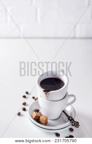 Cup Of Black Coffee On A Saucer With Brown Sugar And Coffee Beans On A White Background With Copy Sp