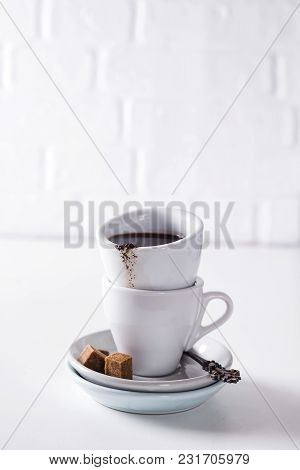 Cup Of Black Coffee On A Saucer With Brown Sugar On A White Background With Copy Space