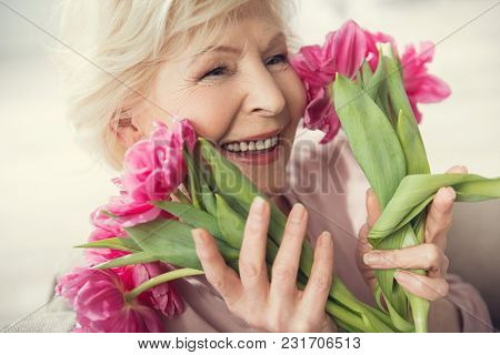 Portrait Of Delighted Gray Haired Granny Holding Beautiful Tulips Close To Her Face And Laughing