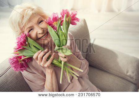 Elderly female person sitting at home with tulips and looking at camera with bliss. Copy space in right side. Top view poster