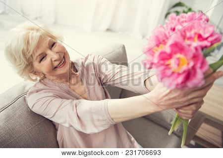 Mature Female Person Resting On Divan Indoors. She Is Holding Up Tulips And Admiring Them. Focus On
