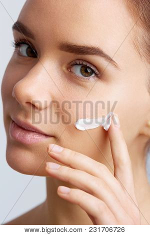 Beautiful Model Applying Cosmetic Cream Treatment On Her Face. Close-up Young Beautiful Face Of Girl