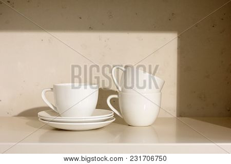 Closeup Of White Ceramic Cups And Saucer On A Shelf